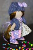 Wenig Flickenpuppe gekleidet im hellblauen Tupfenkleid, blaue Strickmütze mit Bogen Stockbilder