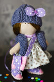 Wenig Flickenpuppe gekleidet im hellblauen Tupfenkleid, blaue Strickmütze mit Bogen, Lizenzfreies Stockfoto