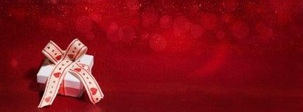 Wenig Geschenk auf einem roten Hintergrund mit bokeh Stockfotografie