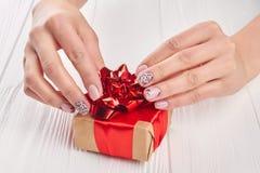Wenig Geschenkbox in Frau manikürten Händen Stockfoto