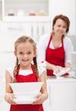 Wenig girtl helfende Mutter, zum der Teller zu tun stockfotografie