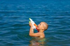 Wenig glückliche Jungenschwimmen im Meer mit glücklicher Kindheit des Wasserwerferkonzeptes stockfotos