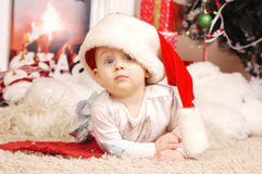 Wenig glückliches Weihnachtsmädchen in Sankt Hut Stockfotos
