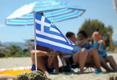 Wenig griechische Flagge im Sand lokalisiert mit unscharfen Leuten Stockbilder