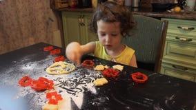 Wenig hübsches Kindermädchen, das Zimt-Lebkuchen-Plätzchen macht Weihnachts- und des neuen Jahreskonzept 2019 rote Plastikformen, stock video footage