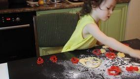 Wenig hübsches Kindermädchen, das Zimt-Lebkuchen-Plätzchen macht Weihnachts- und des neuen Jahreskonzept 2019 rote Plastikformen, stock video