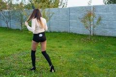 Wenig hübsches Mädchen mit den Haseohren sitzt auf Gras und hält Korb mit farbigen Eiern am bewölkten Tag lizenzfreies stockfoto