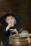 Wenig Halloween-Hexe mit großem Kessel Stockfoto