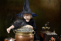 Wenig Halloween-Hexe mit großem Kessel Lizenzfreie Stockfotografie