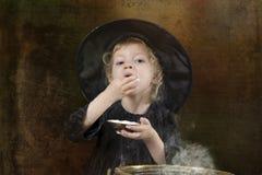 Wenig Halloween-Hexe mit großem Kessel lizenzfreies stockfoto