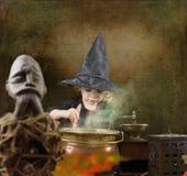 Wenig Halloween-Hexe mit großem Kessel Stockfotos