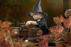 Wenig Halloween-Hexe mit rauchendem großem Kessel Lizenzfreie Stockfotos