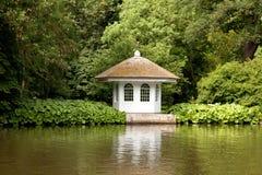 Wenig Haus im reichen Garten auf Damm Lizenzfreie Stockbilder