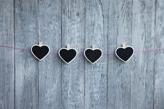 Wenig Herzen auf einem Seil hängen an einem rosa Seil auf einem hölzernen grauen Hintergrund Lizenzfreie Stockfotografie