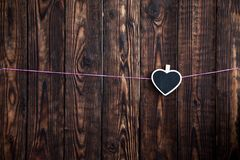 Wenig Herzen auf einem Seil hängen an einem rosa Seil auf einem hölzernen Hintergrund Lizenzfreie Stockfotos