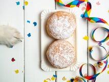 Wenig Hundetatzen- und -donutschaumgummiringe mit Karnevalsdekoration auf einem weißen Hintergrund lizenzfreies stockfoto