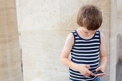 Wenig 7 Jahre alte Junge, die bewegliche Spiele auf Smartphone spielen Stockfotografie