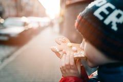 Wenig 7 Jahre alte Junge, die Lebkuchen-Mann essen Stockbild