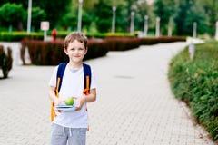 Wenig 7 Jahre alte Junge mit Büchern und Apfel Stockfotos