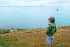 Wenig 6 Jahre alte Junge steht auf Berge und heraus schauen zum Meer Lizenzfreies Stockfoto