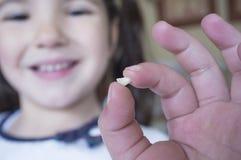 Wenig 5 Jahre alte Mädchen, die ihren ersten Milchzahn herausgefallen zeigen Lizenzfreie Stockfotografie