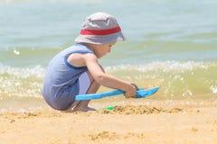 Wenig Junge allein, der auf dem Seestrand mit Sand spielt lizenzfreie stockbilder