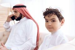 Wenig Junge bittet um Aufmerksamkeit des beschäftigten arabischen Vaters stockbilder
