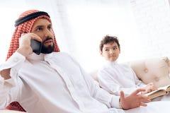 Wenig Junge bittet um Aufmerksamkeit des beschäftigten arabischen Vaters stockfotografie