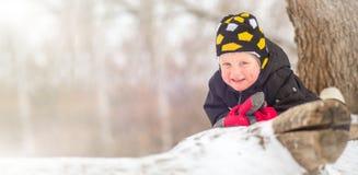 Wenig Junge, der auf dem Schnee im Winter liegt lizenzfreie stockfotos