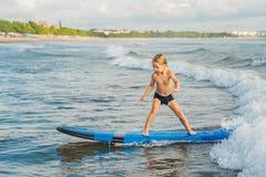 Wenig Junge, der auf tropischen Strand surft Kind auf Brandungsbrett auf Meereswogen Aktiver Wassersport für Kinder Kinderschwimm stockfotos