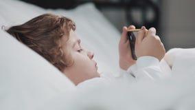 Wenig Junge, der in der aufpassenden Karikatur des Betts am modernen gelben Smartphone mit Interesse liegt stock video