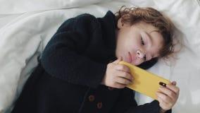 Wenig Junge, der in der aufpassenden Karikatur des Betts am modernen gelben Smartphone mit Interesse liegt stock video footage