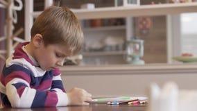 Wenig Junge, der eine lustige Karikatur auf einem Smartphone aufpasst stock video