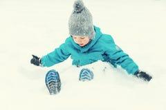 Wenig Junge, der im Schnee und im Lachen spielt stockbild