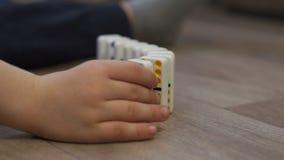 Wenig Junge, der mit Dominos auf dem Boden des Hauses spielt Dominoprinzip stock footage