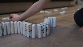 Wenig Junge, der mit Dominos auf dem Boden des Hauses spielt Dominoprinzip stock video footage