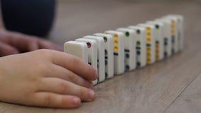 Wenig Junge, der mit Dominos auf dem Boden des Hauses spielt Dominoprinzip stock video