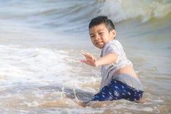 Wenig Junge, der mit Welle und Sand auf Pattaya-Strand spielt stockfoto
