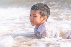 Wenig Junge, der mit Welle und Sand auf Pattaya-Strand spielt lizenzfreies stockbild