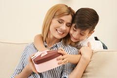 Wenig Junge, der seine Mutter beglückwünscht Glücklicher Mutter`s Tag stockbild