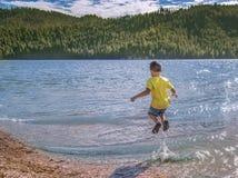 Wenig Junge, der in Wasser springt stockfotografie