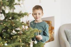 Wenig Junge, der Weihnachtsbaum mit Spielwaren und B?llen verziert stockfoto
