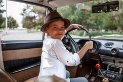 Wenig Junge in der Weinlesekleidung, die innerhalb eines Retro- Autos sitzt lizenzfreie stockfotografie