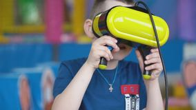 Wenig Junge in einem Sturzhelm der virtuellen Realität spielt Spiele stock footage