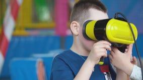 Wenig Junge in einem Sturzhelm der virtuellen Realit?t spielt Spiele stock video footage