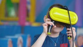 Wenig Junge in einem Sturzhelm der virtuellen Realit?t spielt Spiele stock footage