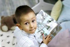 Wenig Junge ist, umarmend sitzend und sein Geschenk stockfotos