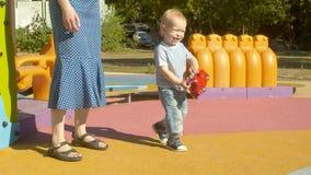 Wenig Junge mit dem Spielzeug auf dem Spielplatz stock video footage