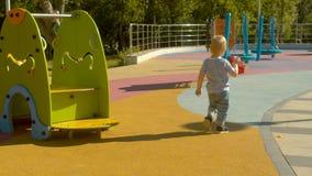 Wenig Junge mit dem Spielzeug auf dem Spielplatz stock video