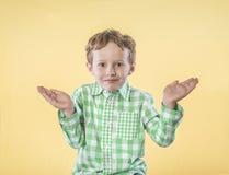 Wenig Junge mit den Händen hob fragliches an stockfotos